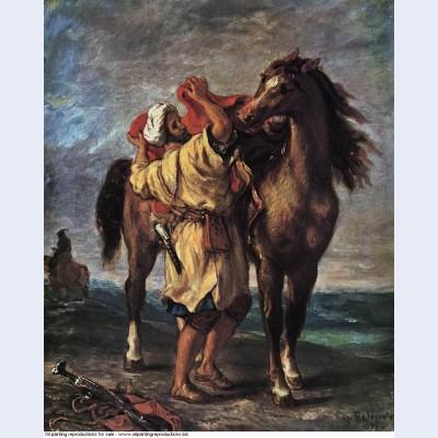 A moroccan saddling a horse 1