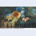 A pumpkin peaches and grapes in a china bowl by glasses on a draped table